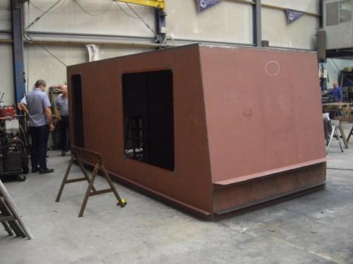 Het duurt niet lang meer of het dekhuis staat op het schip! Het montagegat wordt afgedicht door een aluminium luik.