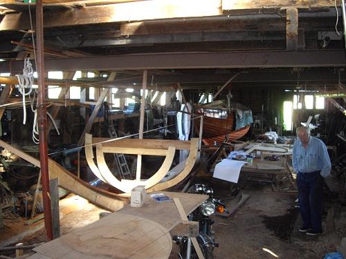 De heer Piet Bouhuijs in zijn werkplaats achter zijn huis te Durgerdam met op de voorgrond de mal van de laatste, door hem te bouwen boot.